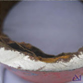A section through the pipe wall showing a large corrosion pit